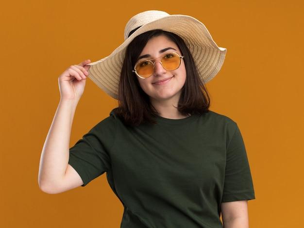 Jovem, bonita, caucasiana, satisfeita, com óculos de sol e chapéu de praia, isolada na parede laranja com espaço de cópia