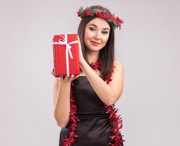 Jovem, bonita, caucasiana, satisfeita, usando coroa de flores de natal e guirlanda de ouropel em volta do pescoço segurando um pacote de presente, olhando para a câmera, isolada no fundo branco com espaço de cópia