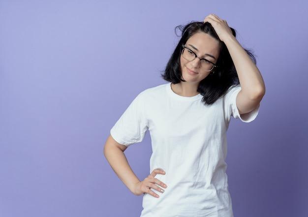Jovem, bonita, caucasiana, satisfeita, usando óculos, colocando as mãos na cabeça e na cintura, olhando para baixo, isolada no fundo roxo com espaço de cópia