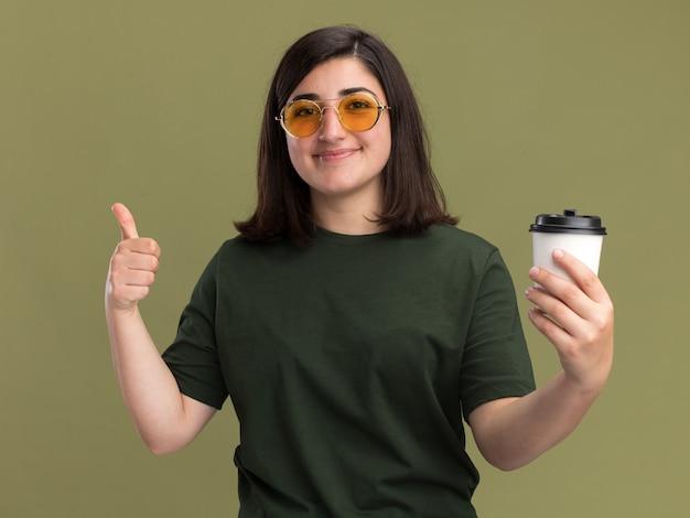Jovem, bonita, caucasiana, satisfeita, usando óculos de sol, polegares para cima e segurando o copo de papel na cor verde oliva