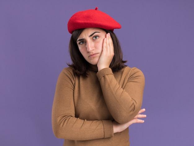 Jovem bonita caucasiana séria com chapéu boina coloca a mão no rosto isolado na parede roxa com espaço de cópia