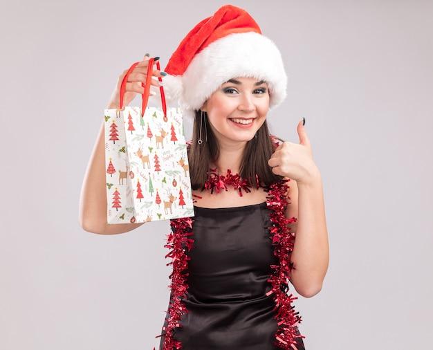 Jovem, bonita, caucasiana, sorridente, com chapéu de papai noel e guirlanda de ouropel em volta do pescoço, olhando para a câmera segurando uma sacola de presente de natal aparecendo o polegar isolado no fundo branco