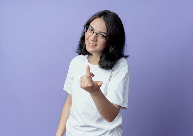Jovem, bonita, caucasiana, sorridente, usando óculos, fazendo gesto de venha cá isolado no fundo roxo com espaço de cópia
