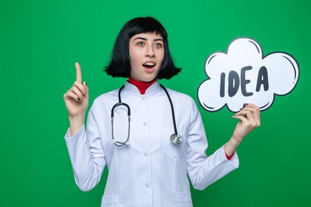 Jovem bonita caucasiana surpresa com uniforme de médico com estetoscópio olhando para o lado apontando para cima e segurando uma bolha de ideia