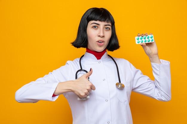 Jovem bonita caucasiana surpresa com uniforme de médico com estetoscópio segurando a embalagem do comprimido e apontando para cima