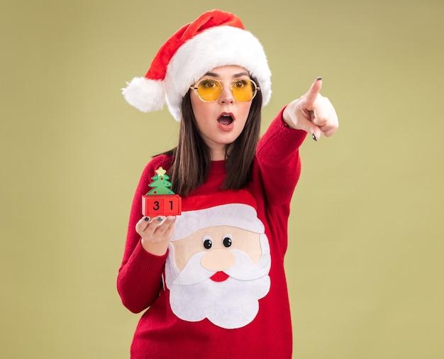 Jovem bonita caucasiana surpresa vestindo blusa de papai noel e bandana com óculos segurando um brinquedo de árvore de natal com data olhando e apontando para o lado isolado no fundo verde oliva