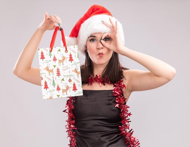 Jovem, bonita, caucasiana, usando chapéu de papai noel e guirlanda de ouropel no pescoço segurando uma sacola de presente de natal, olhando para a câmera, fazendo gesto de olhar franzindo os lábios