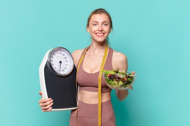 Jovem bonita com expressão feliz de mulher esportiva segurando uma balança e uma salada