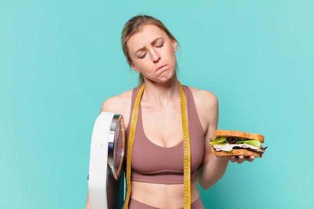 Jovem bonita com expressão triste de mulher esportiva segurando uma balança e um sanduíche