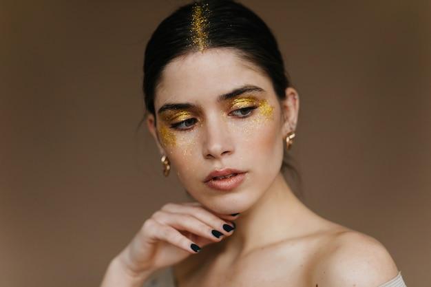 Jovem bonita com maquiagem de brilho posando na parede marrom. close-up da modelo feminina de cabelos negros elegante.