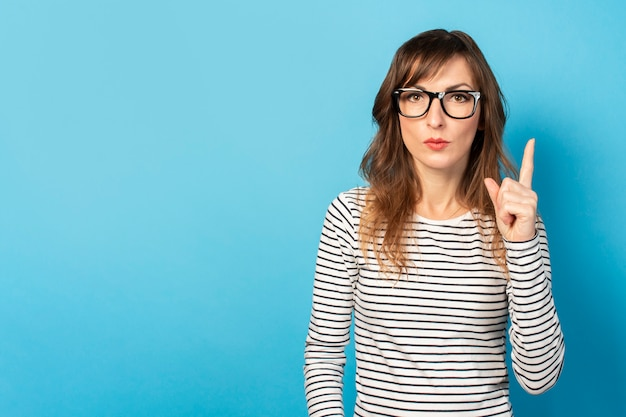 Jovem bonita com óculos e um suéter listrado, um rosto sério aponta um dedo para cima em azul. rosto emocional. o conceito é algo importante, preste atenção