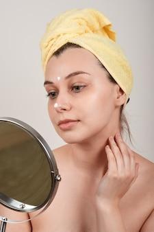 Jovem bonita com ombros nus, toalha amarela na cabeça, aplicação de creme no rosto, olhando no espelho, isolada em uma parede cinza