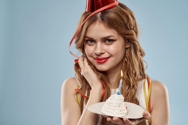 Jovem bonita com um bolinho e velas comemora aniversário, estúdio, parede azul