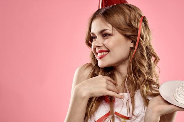 Jovem bonita com um bolinho e velas comemora aniversário, estúdio, parede rosa