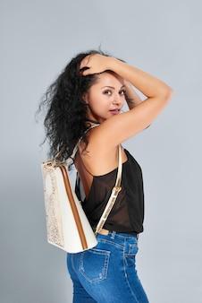 Jovem bonita com um cabelo preto encaracolado, vestindo jeans azul e blusa preta. ela carrega uma mochila branca e marrom nos ombros e uma calça preta no pescoço.