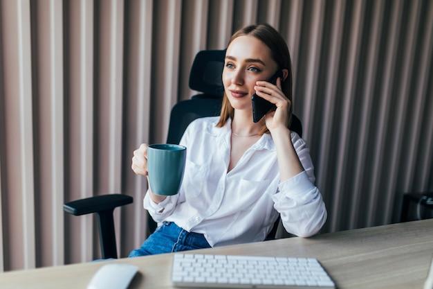 Jovem bonita com um telefone enquanto trabalha no laptop na mesa ao lado da xícara de café