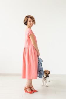 Jovem bonita com um vestido longo rosa, posando com seu amado cachorro em uma parede branca. conceito de roupas casuais elegantes.