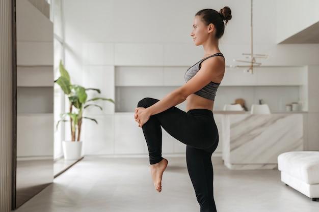 Jovem bonita desportiva no sportswear fazendo alongamento e equilibrando os exercícios de ioga em casa, na sala de estar.