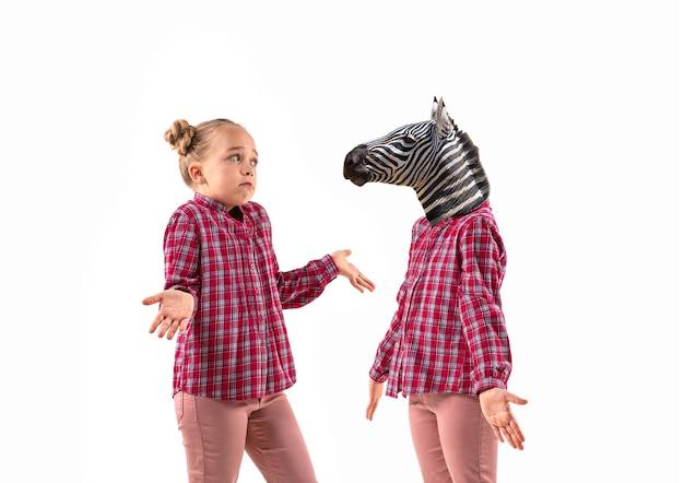 Jovem bonita discutindo consigo mesma como uma zebra no fundo branco do estúdio. conceito de emoções humanas, expressão, problemas mentais, conflito interno, personalidade dividida. conversa agressiva.