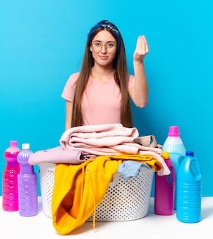 Jovem, bonita dona de casa fazendo capice ou gesto de dinheiro, dizendo para você pagar suas dívidas!