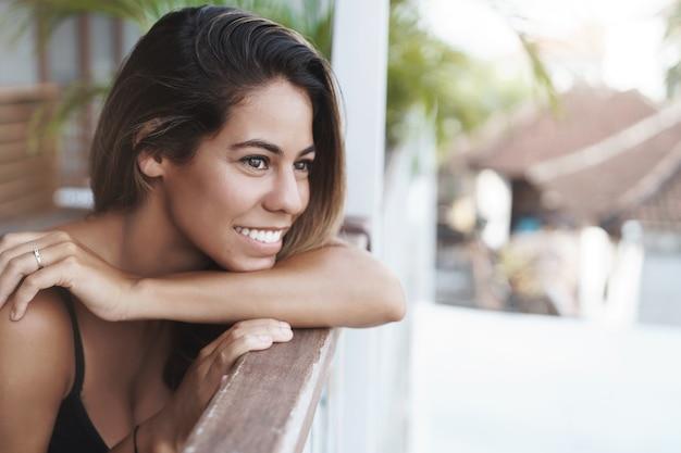 Jovem bonita e alegre, bronzeada, apoiada na grade do terraço e olhando feliz
