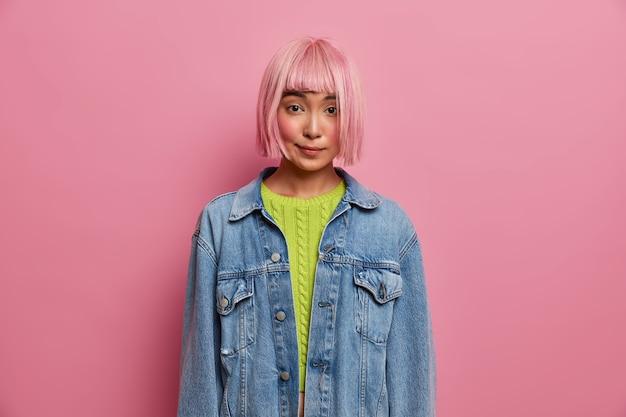 Jovem bonita e atraente tem uma conversa particular, tem um penteado bob, peruca de cabelo rosado e veste uma jaqueta jeans da moda