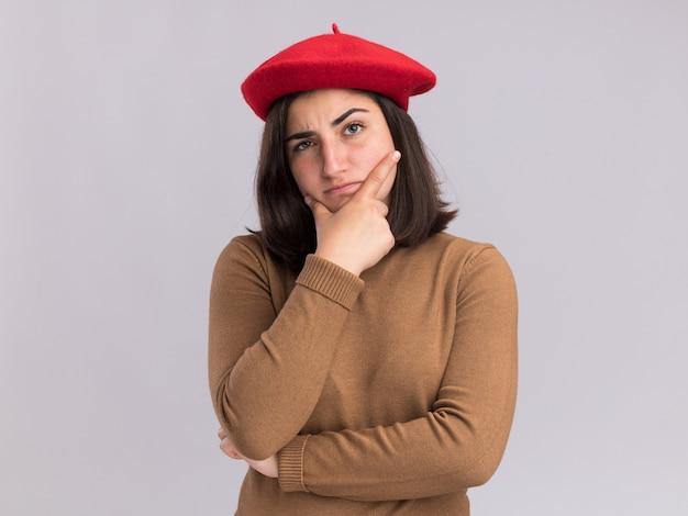 Jovem bonita e confusa, caucasiana, com chapéu de boina segurando o queixo isolado na parede branca com espaço de cópia