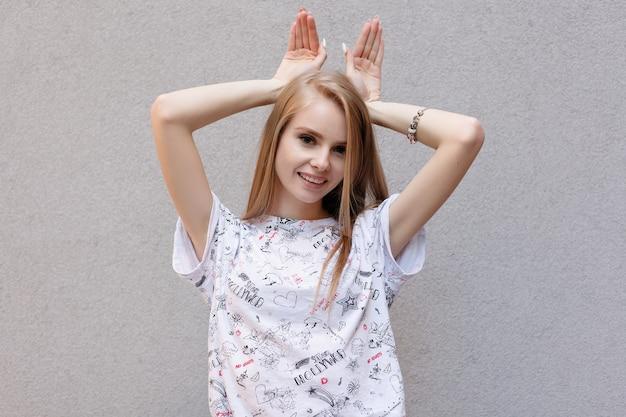 Jovem bonita e feliz aluna caucasiana com longos cabelos castanhos em um macacão e jeans fazendo orelhas de coelho com as mãos, olhando para a câmera com uma expressão divertida e animada