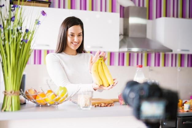 Jovem bonita e fofa está posando para uma câmera enquanto segura bananas em uma cozinha brilhante.
