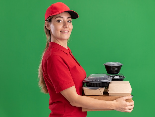 Jovem, bonita e sorridente, entregadora de uniforme parada de lado segurando pacotes de comida de papel