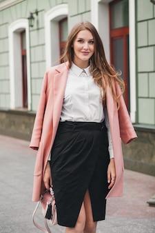 Jovem bonita elegante mulher bonita andando na rua, vestindo casaco rosa, bolsa, camisa branca, saia preta, roupa da moda, tendência de outono, sorrindo feliz, acessórios