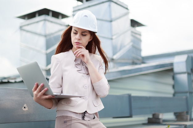 Jovem, bonita empresária em terno bege, calça marrom e capacete sentar no telhado e segurar o laptop
