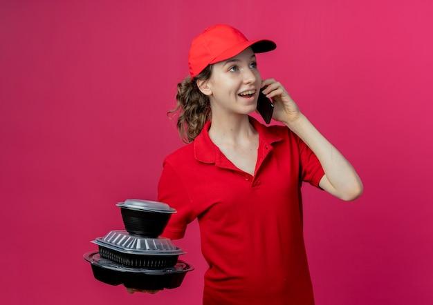 Jovem bonita entregadora alegre vestindo uniforme vermelho e boné, falando no telefone e segurando recipientes de comida, olhando para o lado no espaço carmesim
