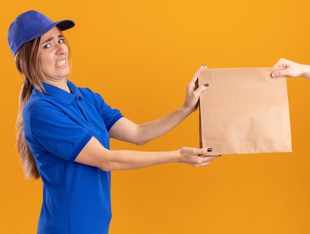 Jovem, bonita, entregadora de uniforme, descontente dando um pacote de papel para alguém olhando para a câmera em laranja