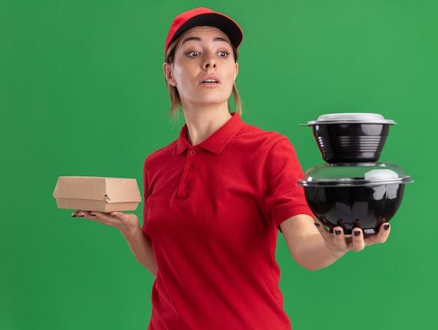 Jovem, bonita, entregadora de uniforme, impressionada segurando um pacote de comida e olhando para os recipientes de comida no verde