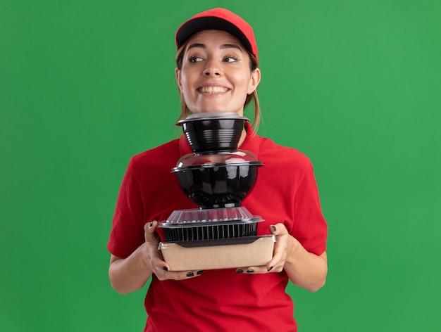 Jovem bonita entregadora de uniforme satisfeita segurando recipientes de comida no verde