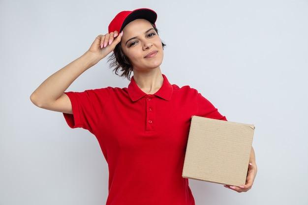 Jovem bonita entregadora satisfeita segurando uma caixa de papelão