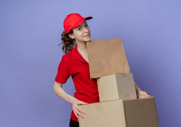 Jovem, bonita, entregadora, satisfeita, vestindo um uniforme vermelho e boné, segurando caixas de papelão e um pacote de papel isolado em um fundo roxo com espaço de cópia