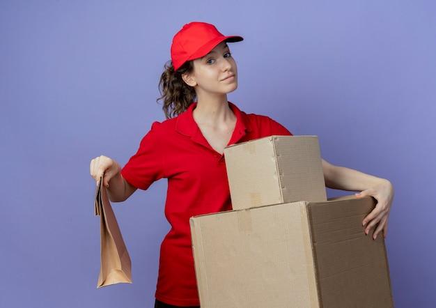 Jovem, bonita, entregadora satisfeita, vestindo um uniforme vermelho e boné segurando caixas de papelão e um pacote de papel isolado no fundo roxo