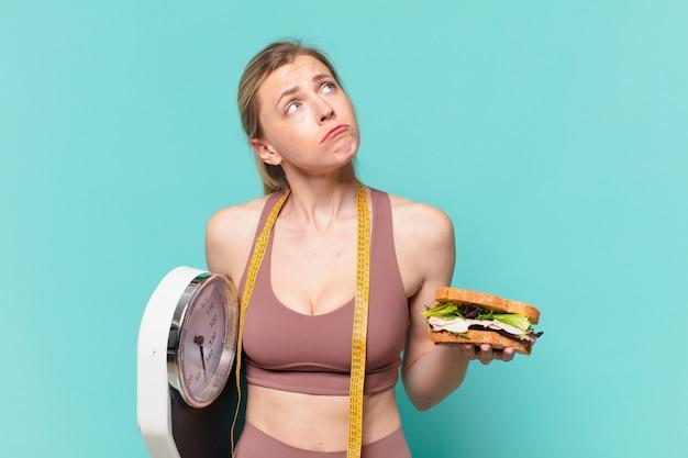 Jovem, bonita, esportista, duvidando ou com uma expressão incerta, segurando uma balança e um sanduíche