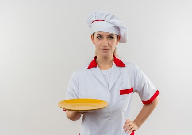 Jovem bonita feliz em uniforme de chef, segurando o prato vazio e colocando a mão na cintura, isolada no espaço em branco