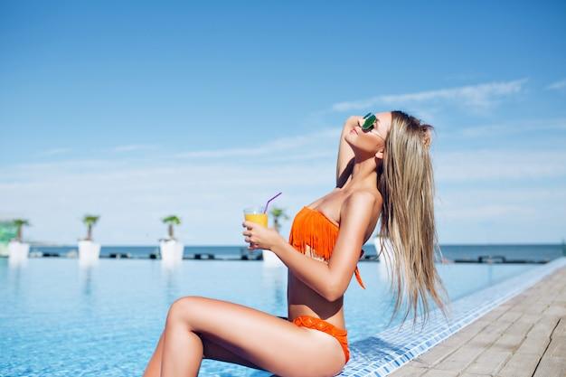 Jovem bonita garota com cabelo comprido está sentada perto da piscina no sol. ela segura o coquetel e parece ter gostado.