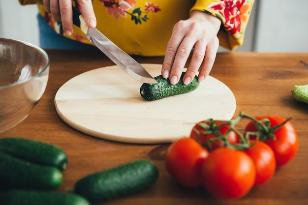 Jovem bonita grávida preparando salada de legumes na cozinha