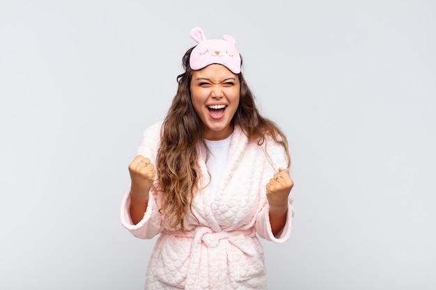 Jovem bonita gritando agressivamente com uma expressão de raiva ou com os punhos cerrados celebrando o sucesso de pijama