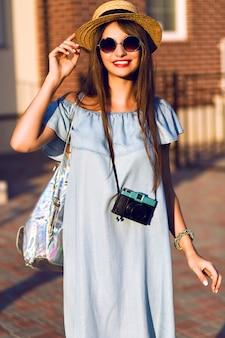 Jovem bonita hippie alegre mulher posando na rua em dia ensolarado, se divertindo sozinho, chapéu e óculos de sol elegantes roupas vintage, conceito de viagens, jovem fotógrafo com câmera vintage.