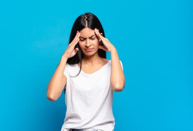 Jovem, bonita, hispânica, parecendo estressada e frustrada, trabalhando sob pressão, com dor de cabeça e preocupada com problemas
