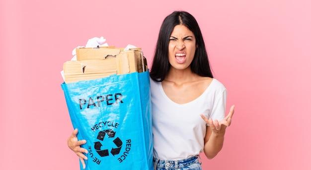 Jovem, bonita, hispânica, parecendo zangada, irritada e frustrada, segurando um saco de papel para reciclar
