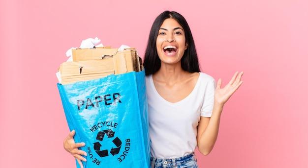 Jovem bonita hispânica se sentindo feliz e surpresa com algo inacreditável e segurando um saco de papel para reciclar