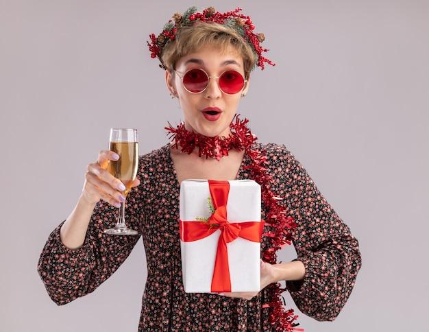 Jovem bonita impressionada com a coroa da cabeça de natal e guirlanda de ouropel ao redor do pescoço, óculos segurando um pacote de presente e uma taça de champanhe, olhando para a câmera, isolada no fundo branco