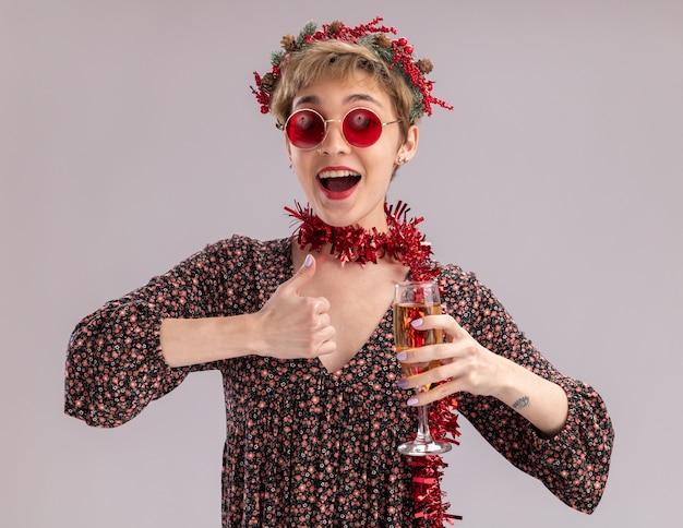 Jovem bonita impressionada com a coroa da cabeça de natal e guirlanda de ouropel em volta do pescoço, com óculos segurando uma taça de champanhe, olhando para a câmera mostrando o polegar isolado no fundo branco